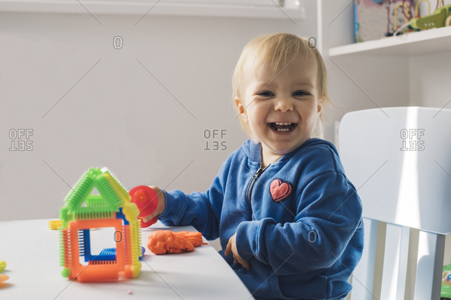 Portrait of laughing baby girl playing with modeling clay