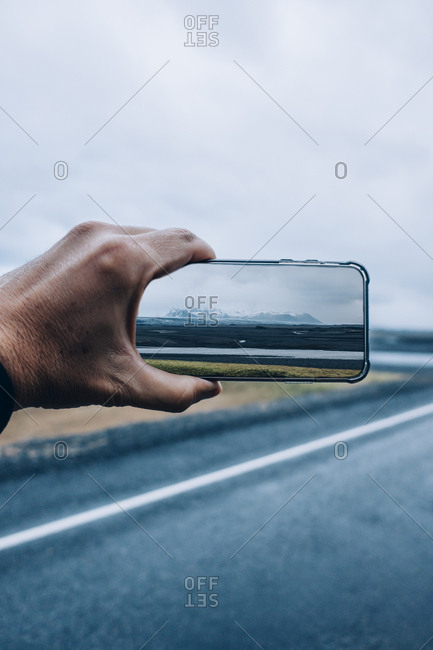 3D montage of man taking smartphone picture of Iceland's landscape