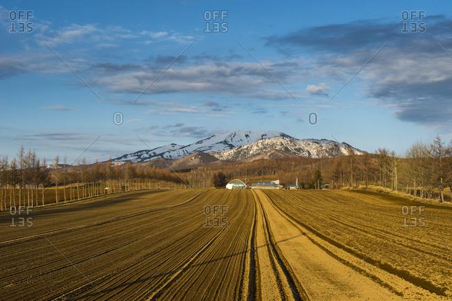 Hokkaido- Little farm before a snow capped mountain near Shiretoko National Park