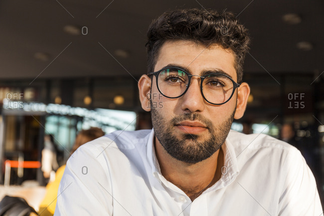Portrait of pensive young businessman with beard and glasses at sidewalk cafe