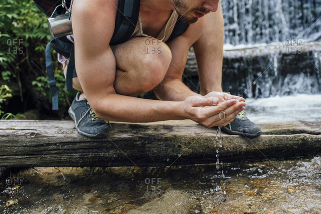 Young hiker with backpack refreshing at water in a forest- partial view