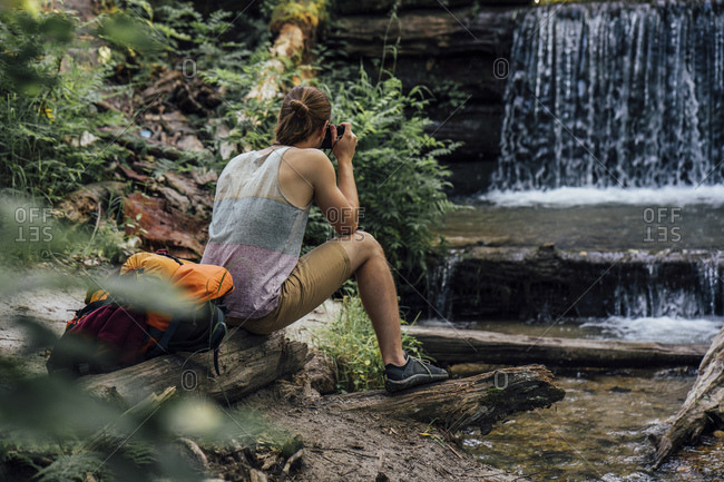 Back view of hiker in a forest taking photo of waterfall