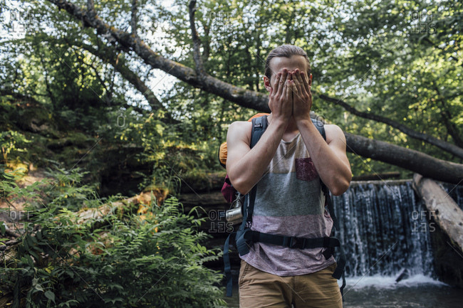 Young man with backpack refreshing at water in a forest