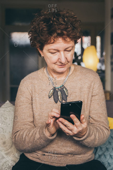 Candid portrait of mature woman surfing the internet on smartphone in her home