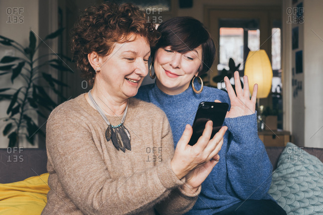 Candid moment, mother and daughter having fun taking a selfie at home