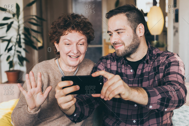 Candid moment, mature woman and son in law having fun taking a selfie at home
