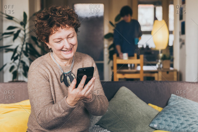 Candid portrait of happy mature woman surfing the internet on smartphone while daughter brings coffee at home