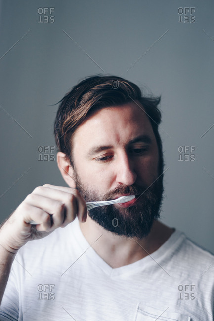 Handsome man in his 30s brushing teeth at home in the morning.