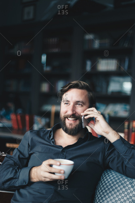 Authentic portrait of handsome  businessman sitting at cafe bar and talking on cell phone.