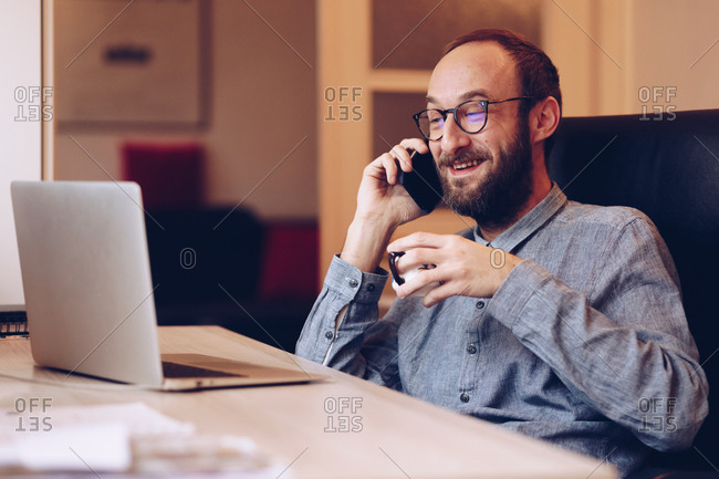 Portrait of young adult in his 30s talking on smartphone to a friend while drinking coffe and surfing the internet
