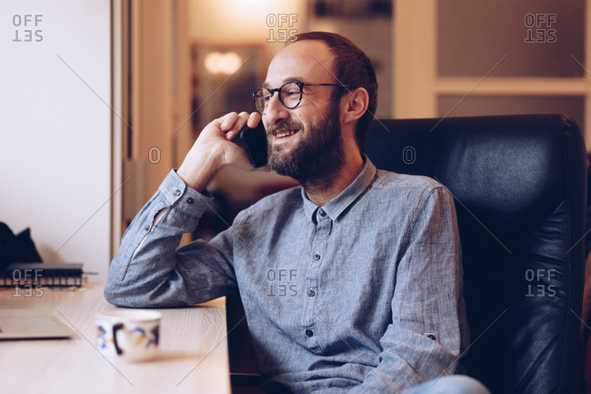 Portrait of happy young adult in his 30s wearing eyeglasses and talking on smartphone to a friend