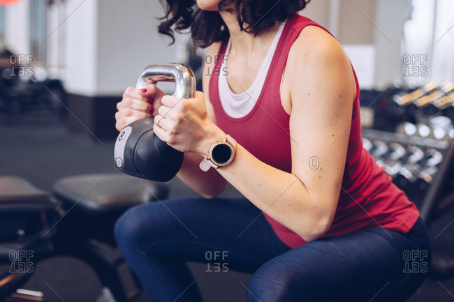 Close up of fit woman doing a squat with dumbell and wearing sport watch