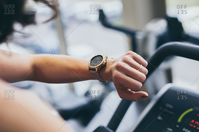Detail of woman checking time on digital smart watch while exercising in the gym