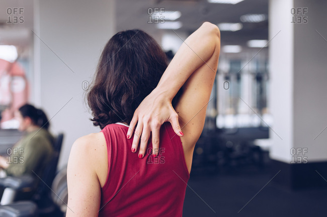 Close up of fit woman stretching arms after workout at gym