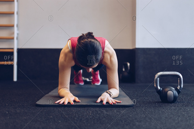 Fit woman doing a plank in the gym