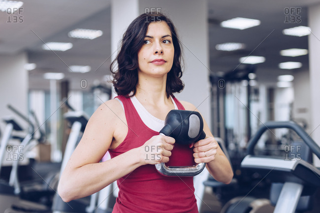 Attractive woman working out by lifting dumb bell