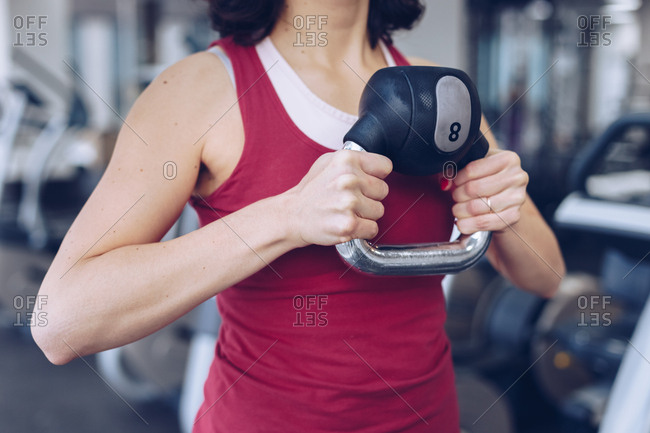 Attractive woman working out by lifting kettle bell