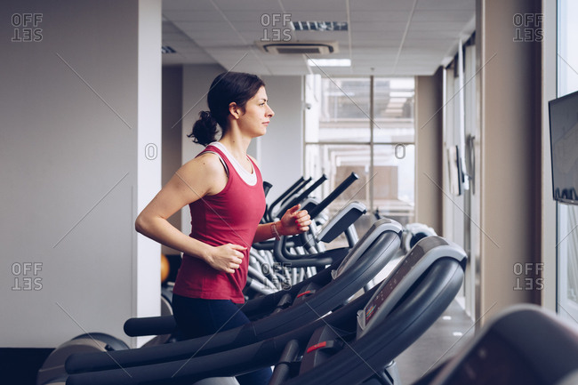Fit young woman running on treadmill in gym, concept of healthy living