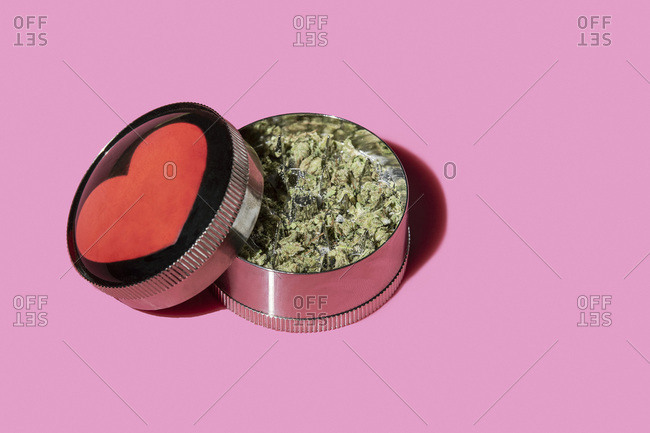 Marijuana in a grinder with a heart on it.