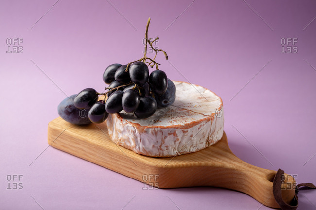 Cheese and fruit on cutting board