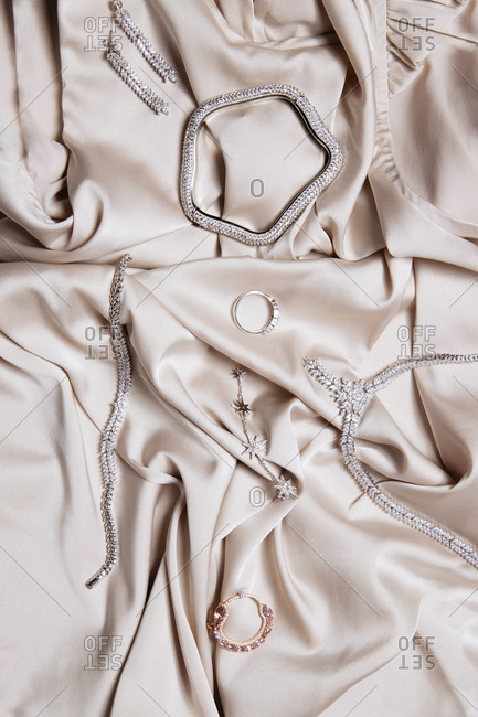 White gold and diamond accessories on beige satin fabric