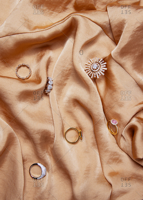 Collection of rings on a cascading orange satin fabric