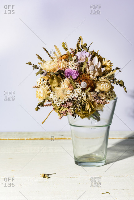 Assorted drying bunch of flowers in vase on wooden table