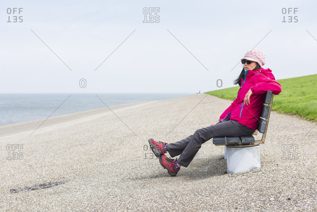 Young lady sitting on the bench watching the sea