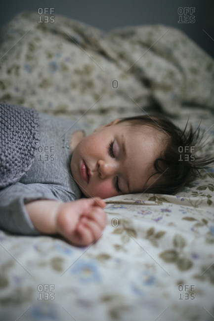 Sleeping baby with dark hair on floral sheets