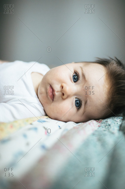 Portrait of a blue eyed baby girl on a quilt