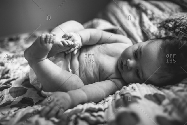 Baby in a diaper on a bed touching her toes in black and white