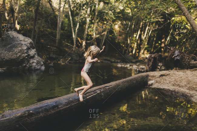 Little girl jumping into a river
