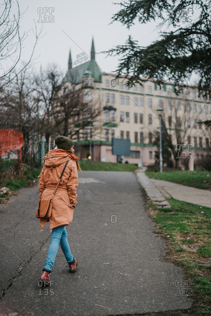 Young woman in a orange jacket casually walking in a park