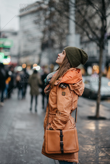 Pretty young woman in orange jacket standing still and looking up above