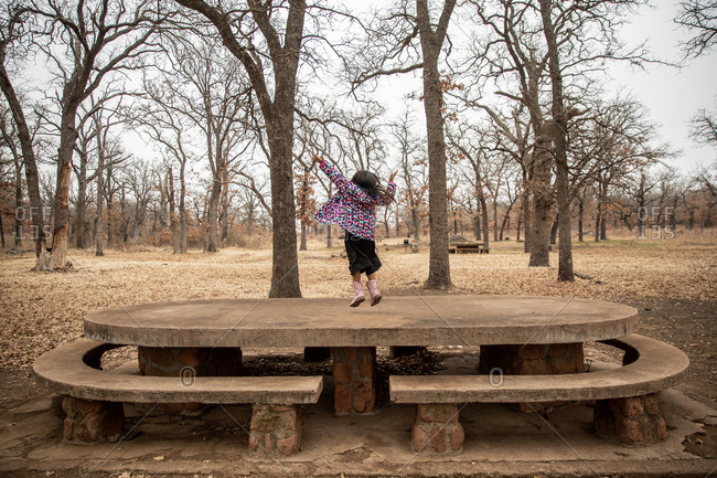 Girl jumping on stone picnic table in the woods