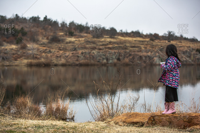 Girl wearing butterfly jacket looking out at lake