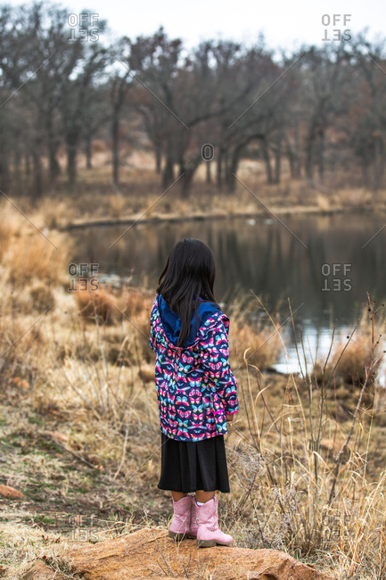 Girl wearing butterfly jacket looking out at a pond