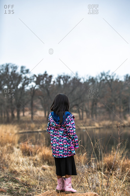 Young girl wearing butterfly jacket looking out at a pond