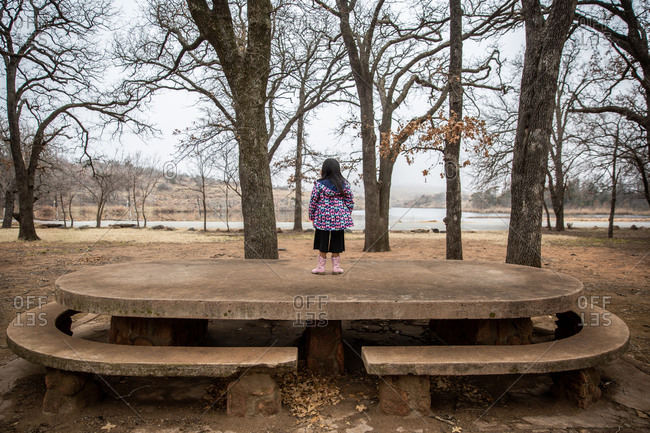 Girl standing on stone picnic table in the woods