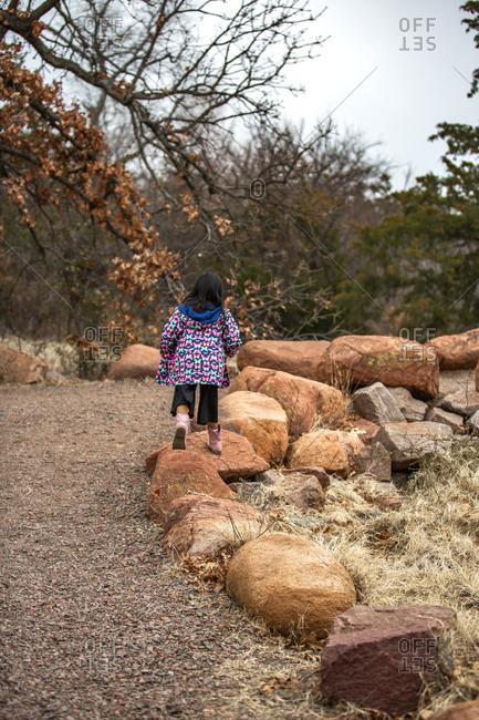 Girl wearing butterfly jacket walking on large stones