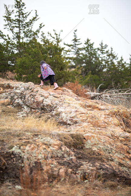 Girl wearing butterfly jacket hiking on rocky mountain