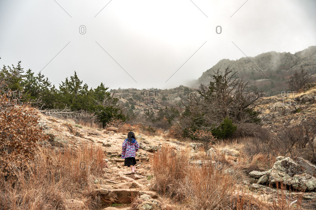 Girl wearing butterfly jacket hiking on foggy mountain