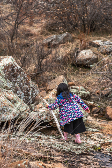 Girl wearing butterfly jacket grabbing stick while hiking