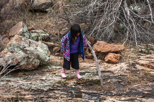 Girl wearing butterfly jacket playing with a stick while hiking