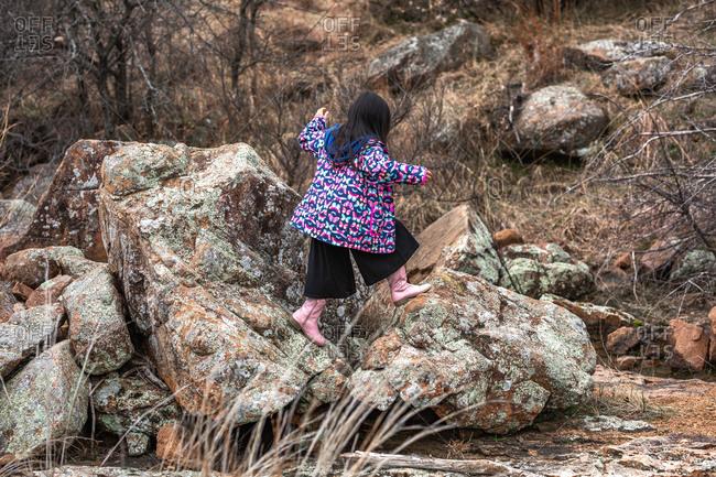 Girl wearing butterfly jacket walking on large rocks