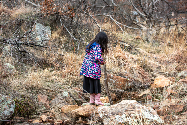 Young girl wearing butterfly jacket hiking while holding a stick