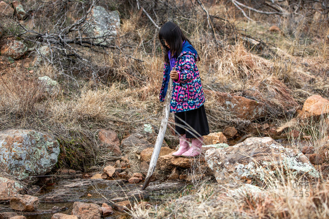 Young girl wearing butterfly jacket playing with stick while hiking