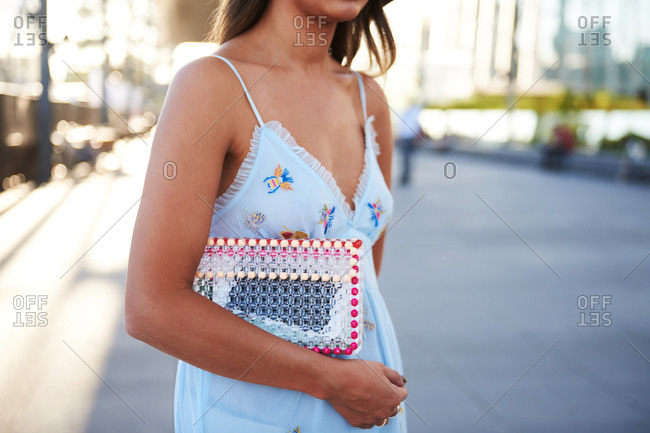 March 09, 2018- Melbourne, Australia: Chic woman wearing light blue summer dress and transparent clutch bag