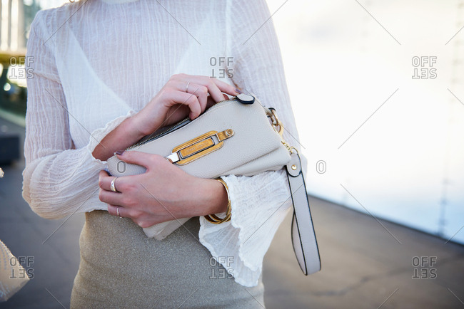 March 09, 2018- Melbourne, Australia: Stylish young woman in neutral summer outfit holding Jimmy Choo purse