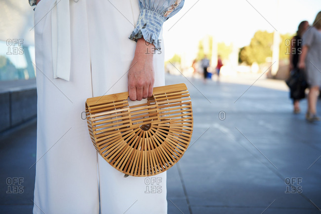 March 09, 2018- Melbourne, Australia: Stylish young woman holding Cult Gaia half moon statement bag